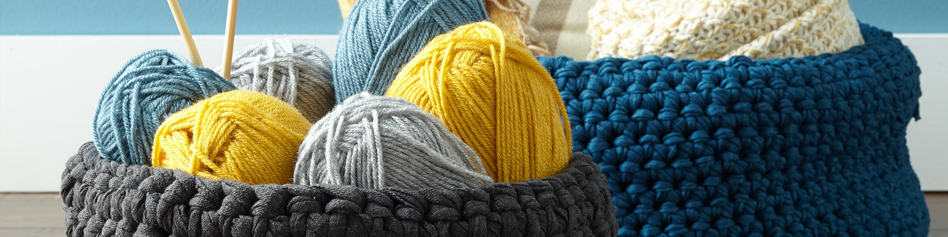 yarn and needles in crocheted baskets