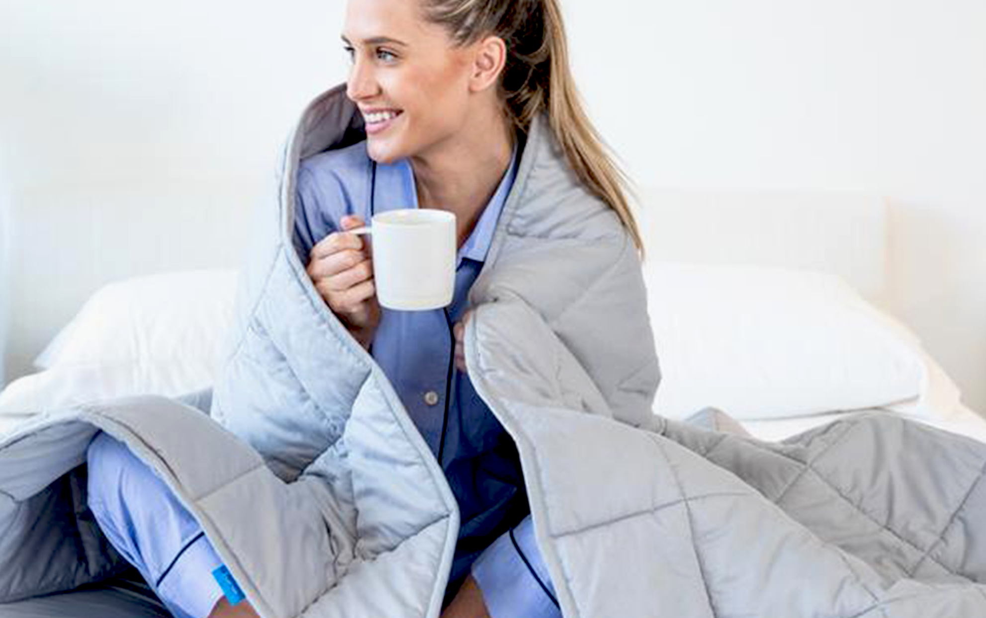 woman drinking coffee in bed with a blanket wrapped around her