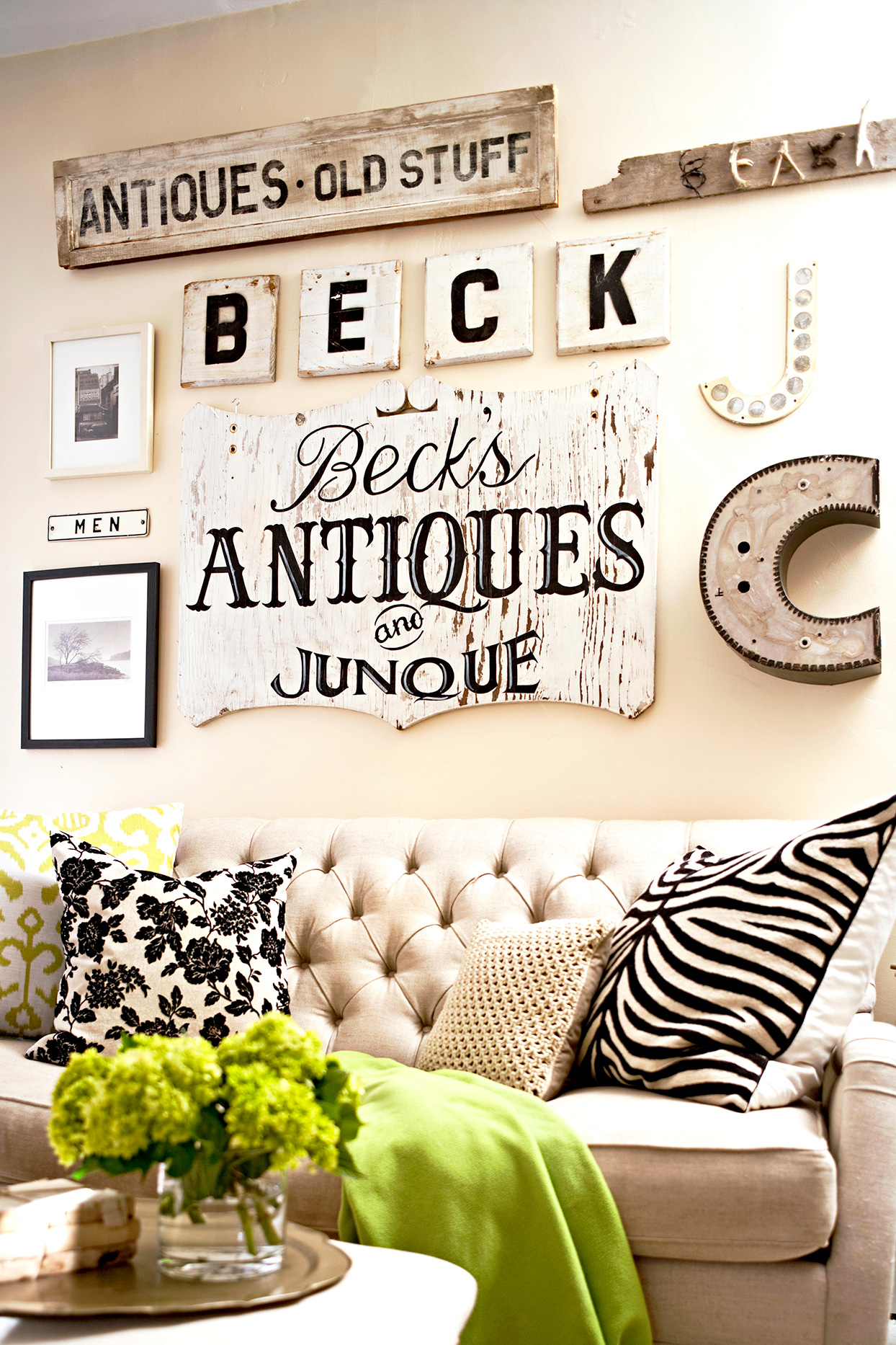 Antique signage in black and white over tufted sofa