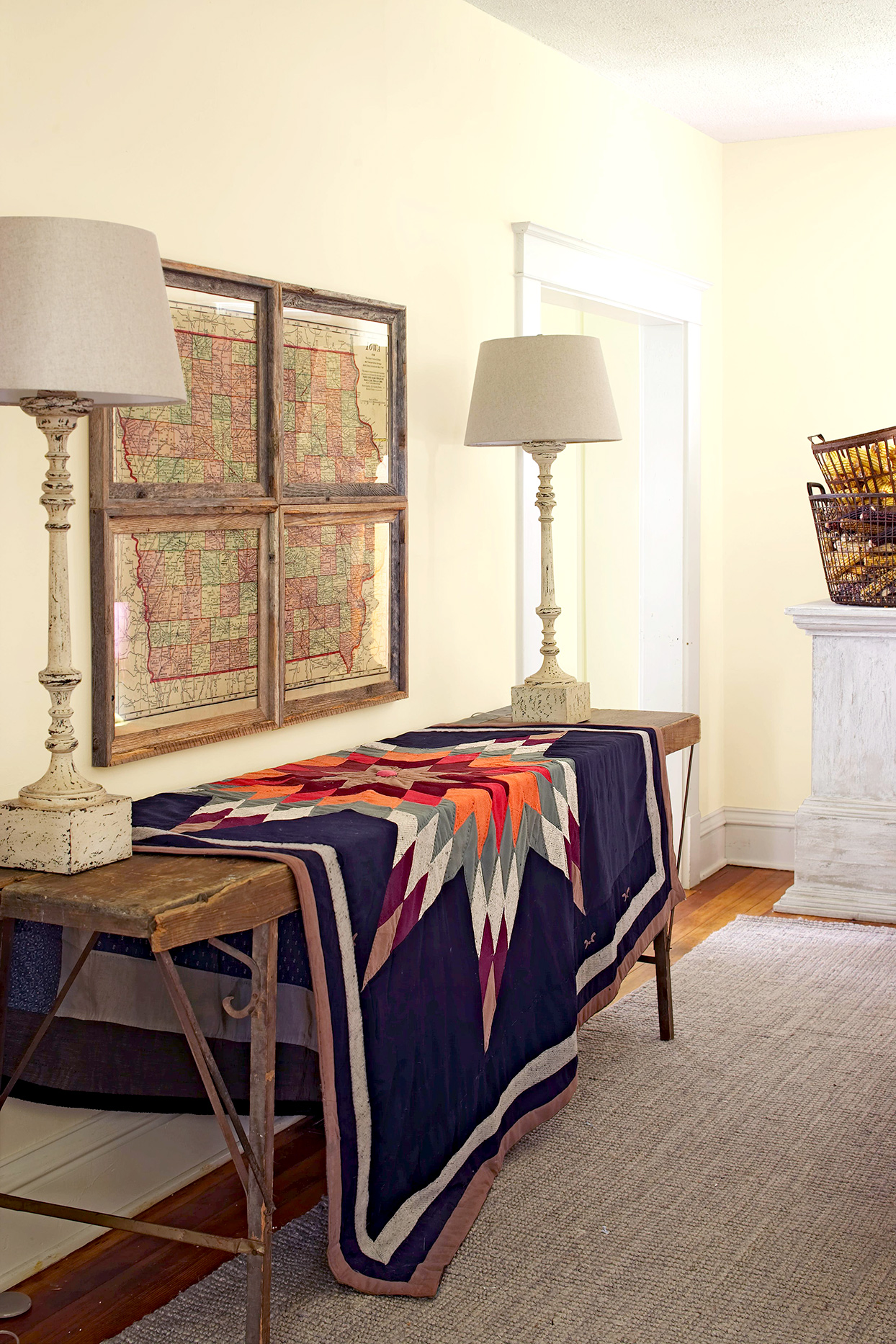Wooden table with quilt and map artwork