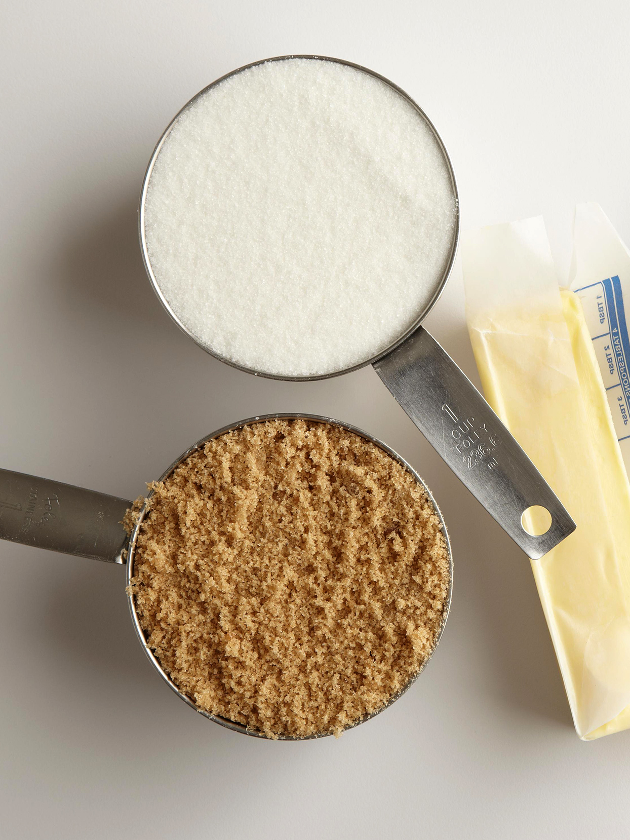 two measuring cups of white and brown sugar