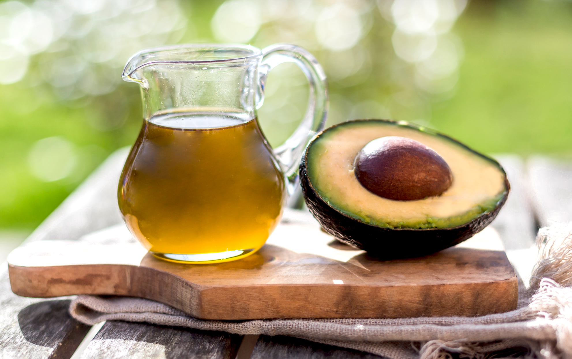 avocado and avocado oil on a cutting board outdoors