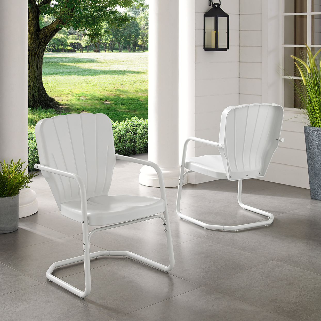 two white metal patio chairs on porch