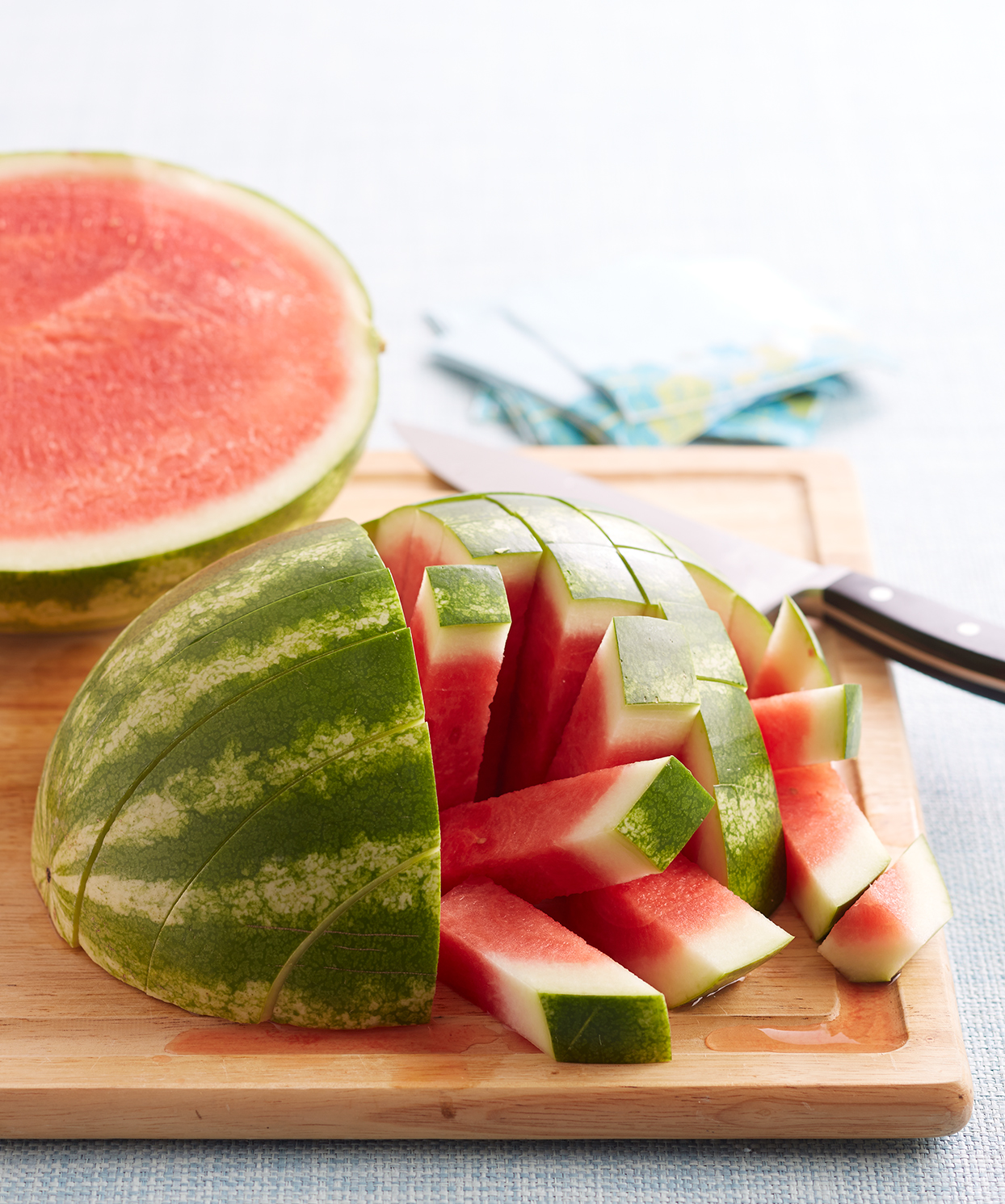 sliced watermelon on cutting board with knife