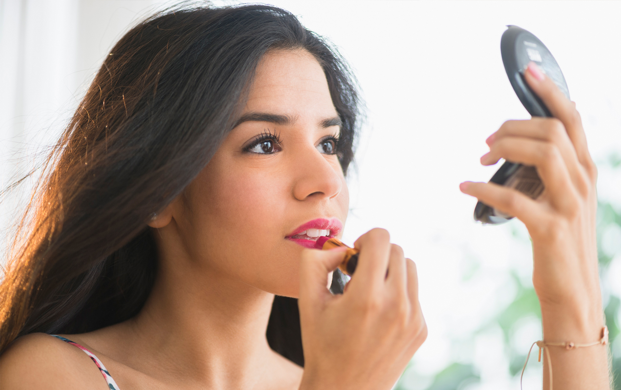 woman applying lipstick while looking at a small mirror