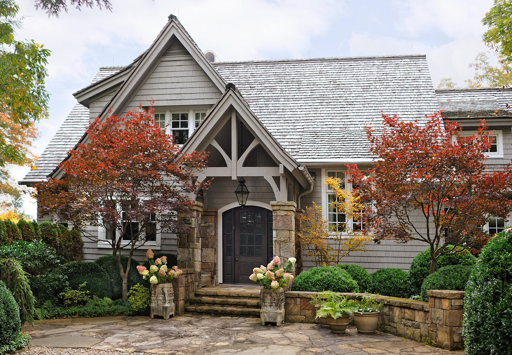 fall foliage and gray home exterior with stone pillars