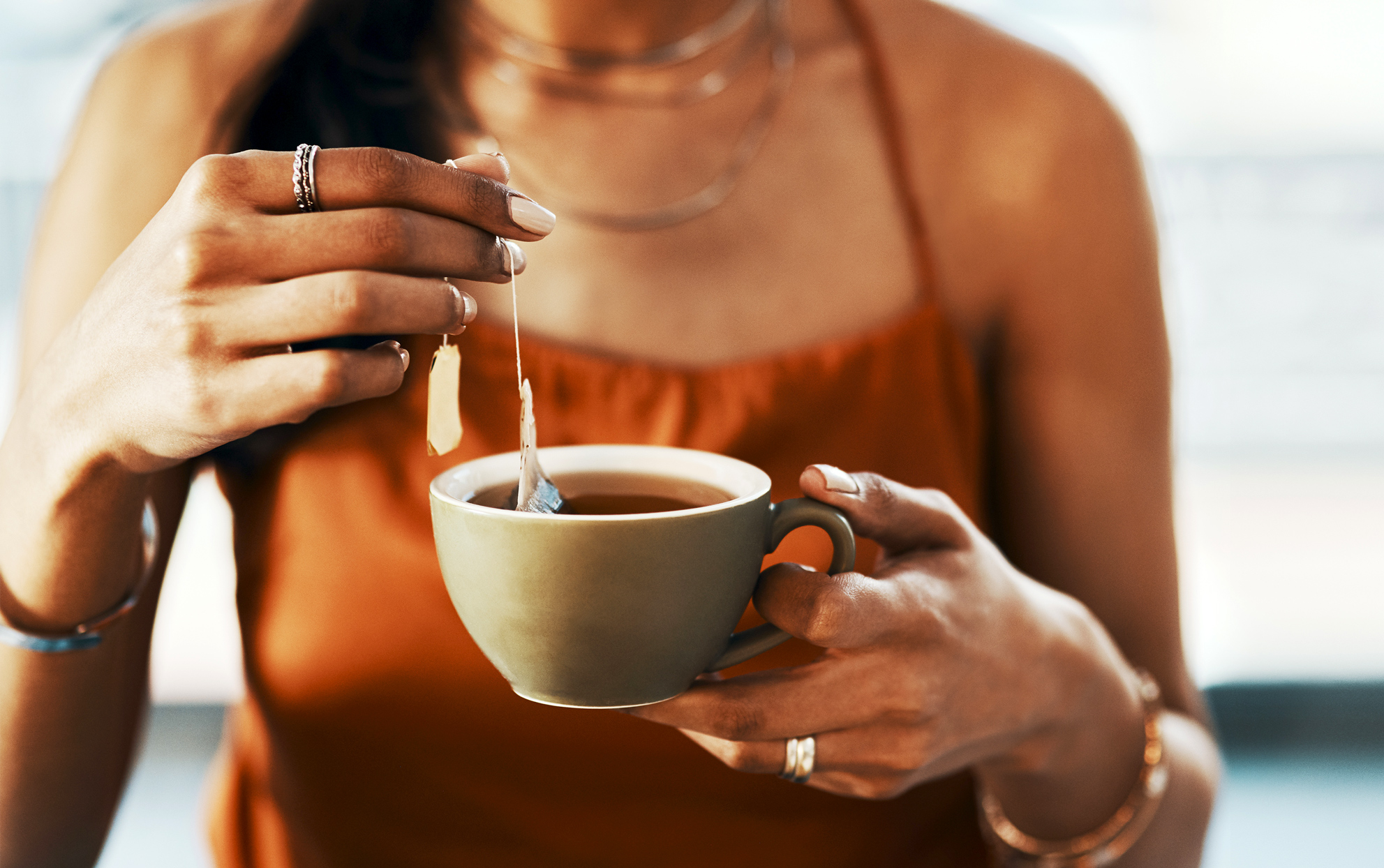 woman holding a cup of tea and a tea bag