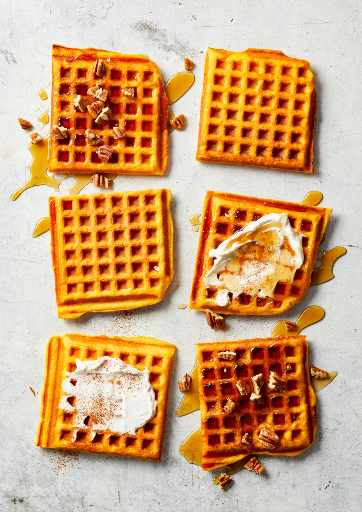 overhead view of sweet potato waffles with syrup, cream, and pecans
