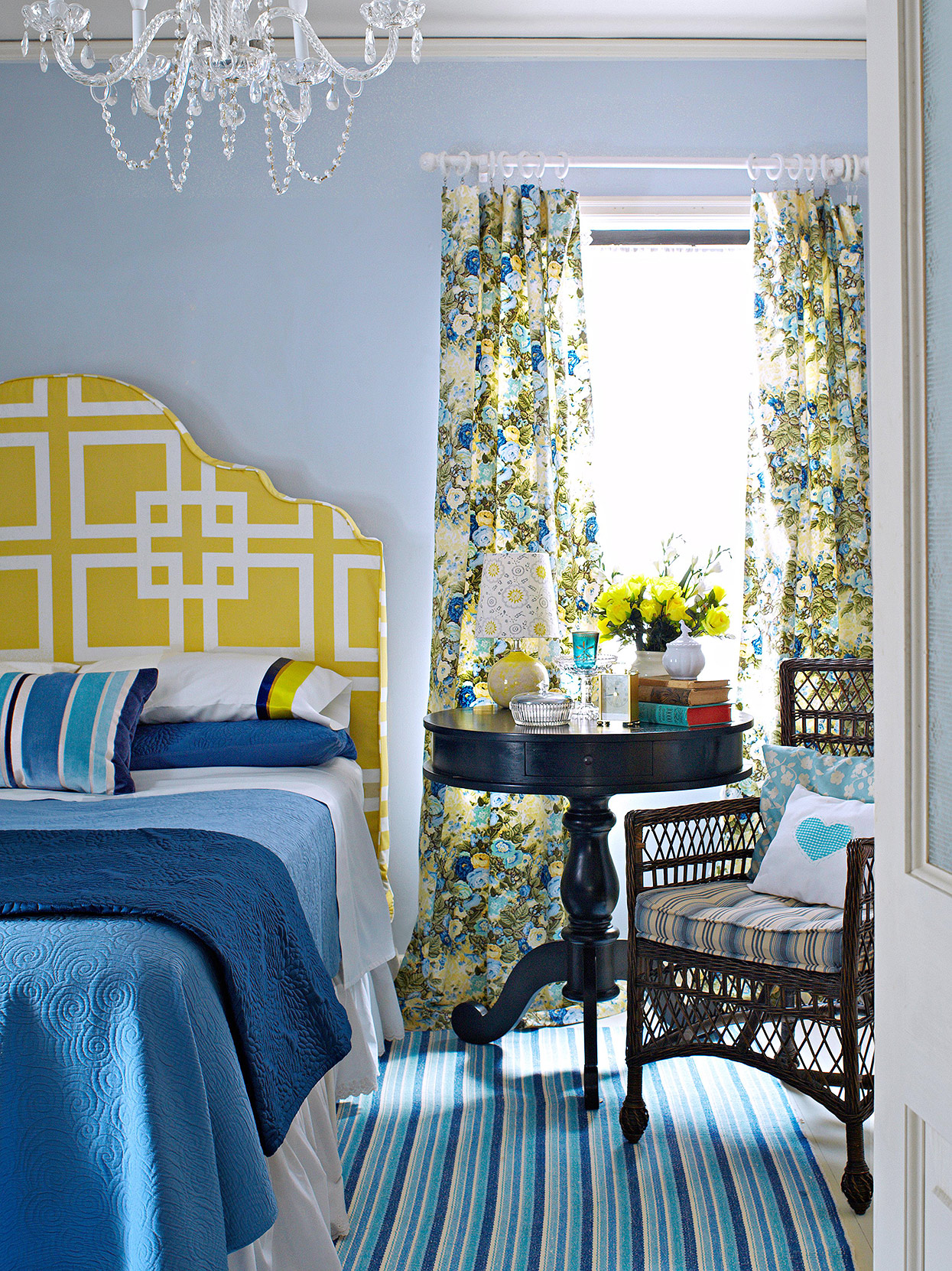 floral panels and yellow geometric headboard in blue room