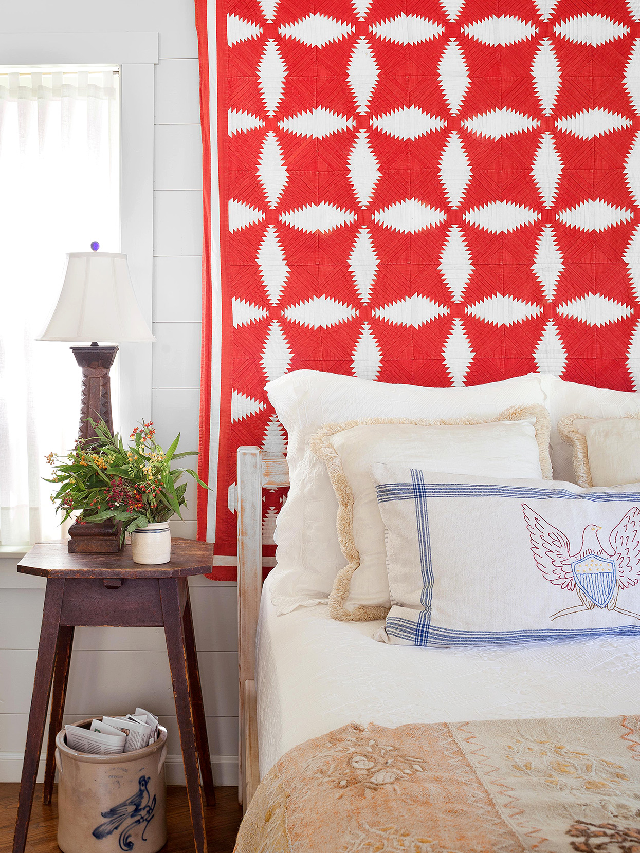 bright red quilt tapestry behind cottage bed