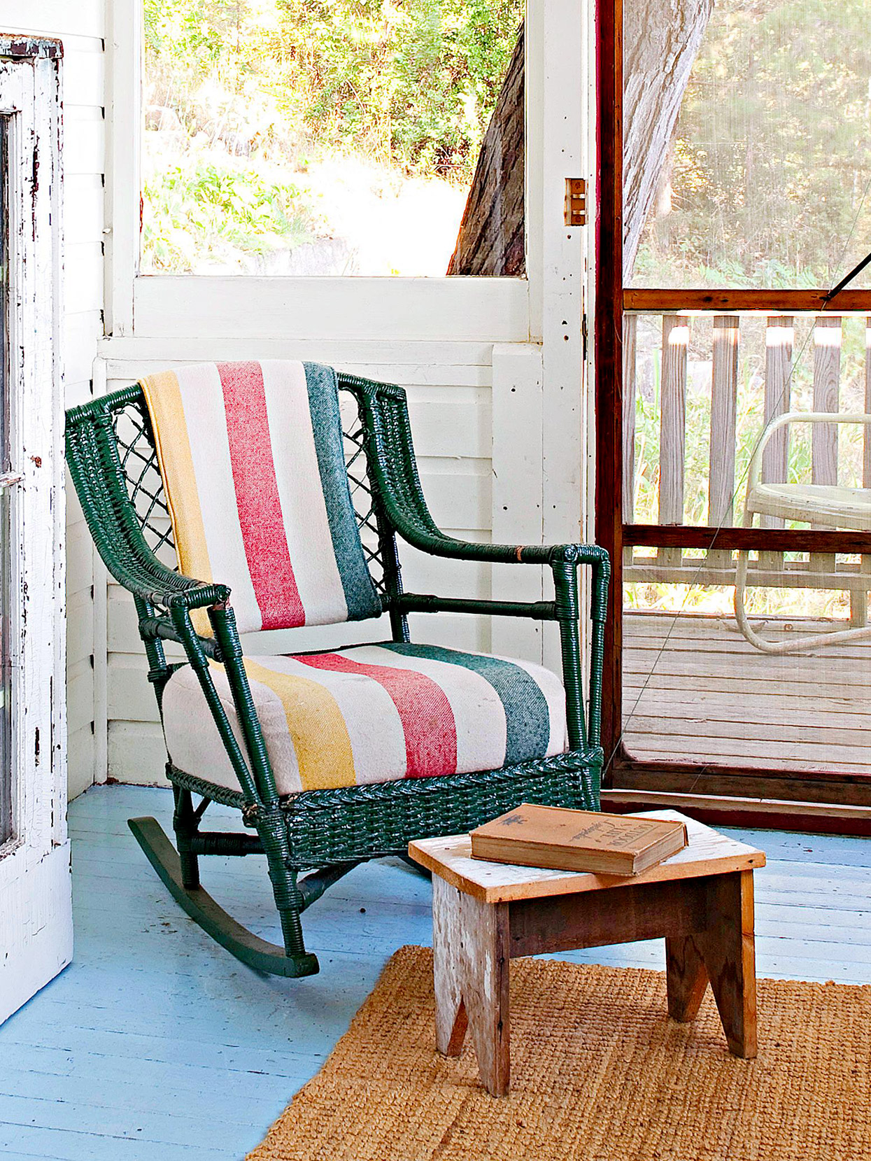 wicker chair with old camp blanket on rustic enclosed porch