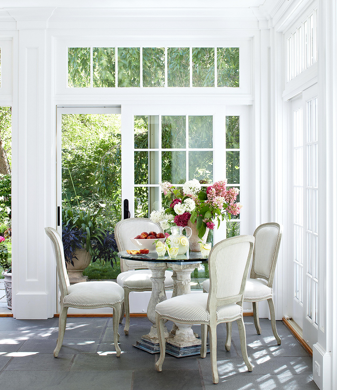sunroom corner with white dining chairs and table