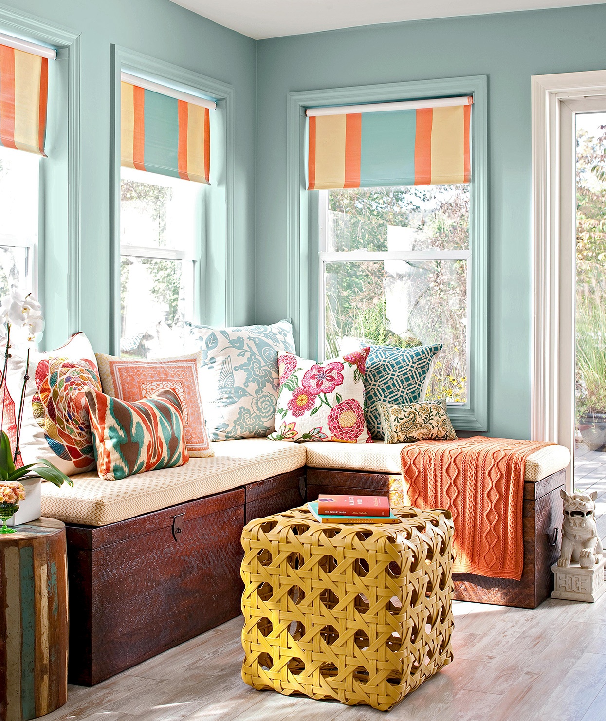 turquoise sunroom corner with chests and cushions for seating