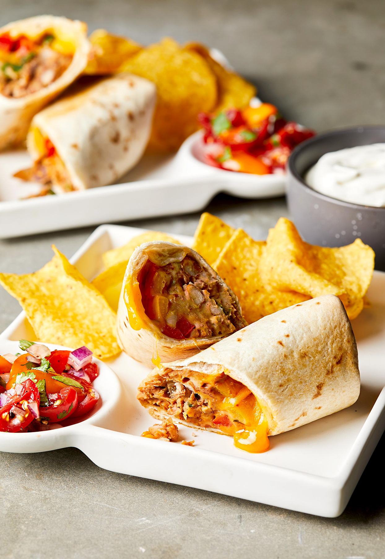 Pinto Bean Burritos on platter with salsa and tortilla chips