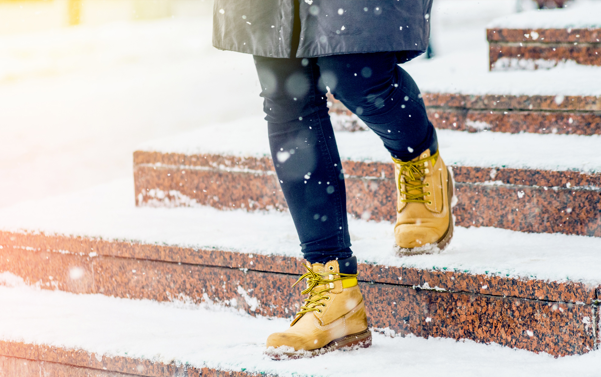 close up of a woman wearing boots walking down stairs in the snow