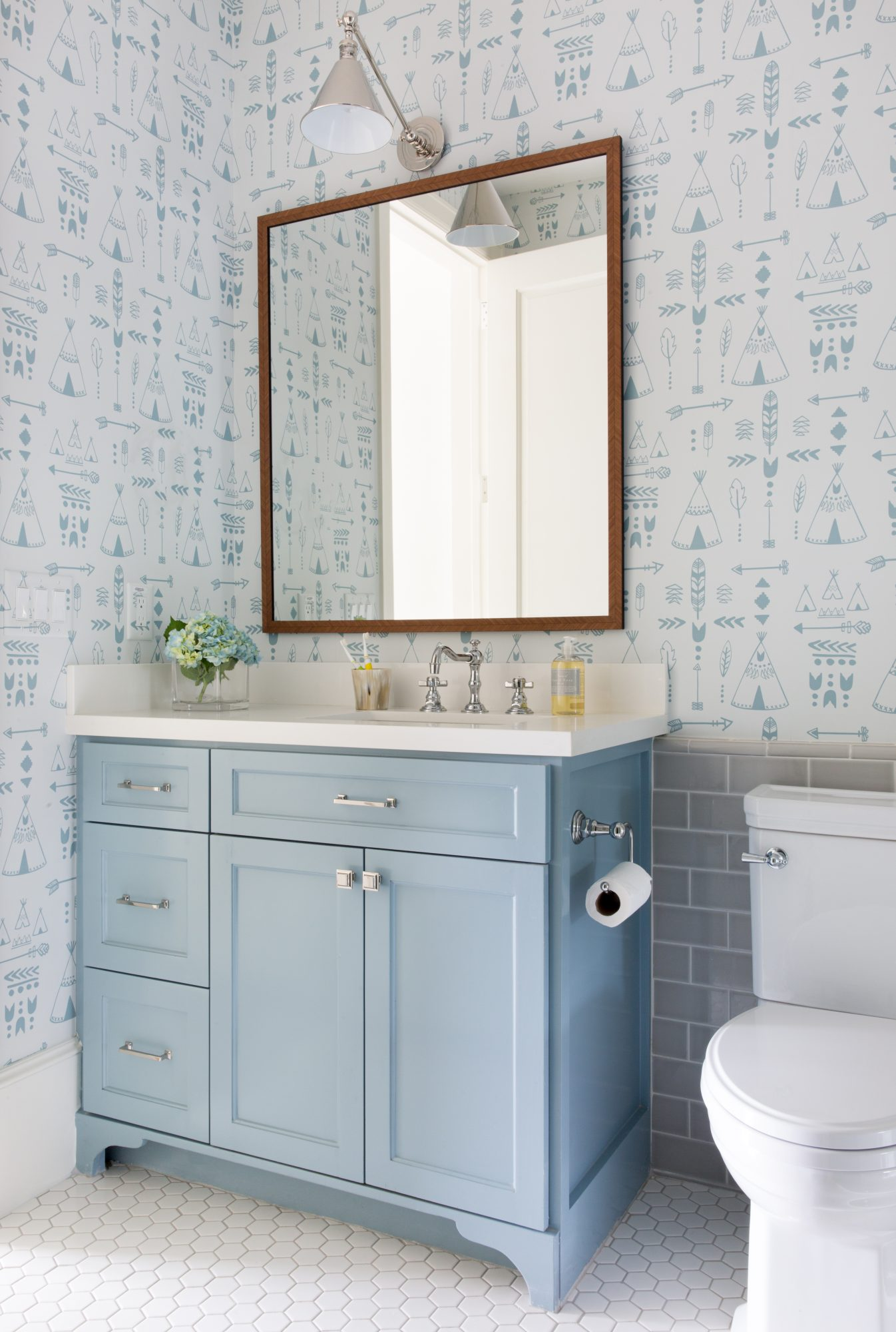 bathroom with blue vanity and patterned wallpaper