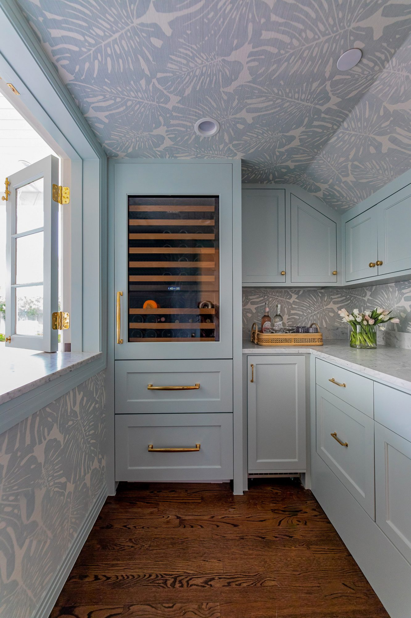 light blue cabinets and walls with blue print wallpaper