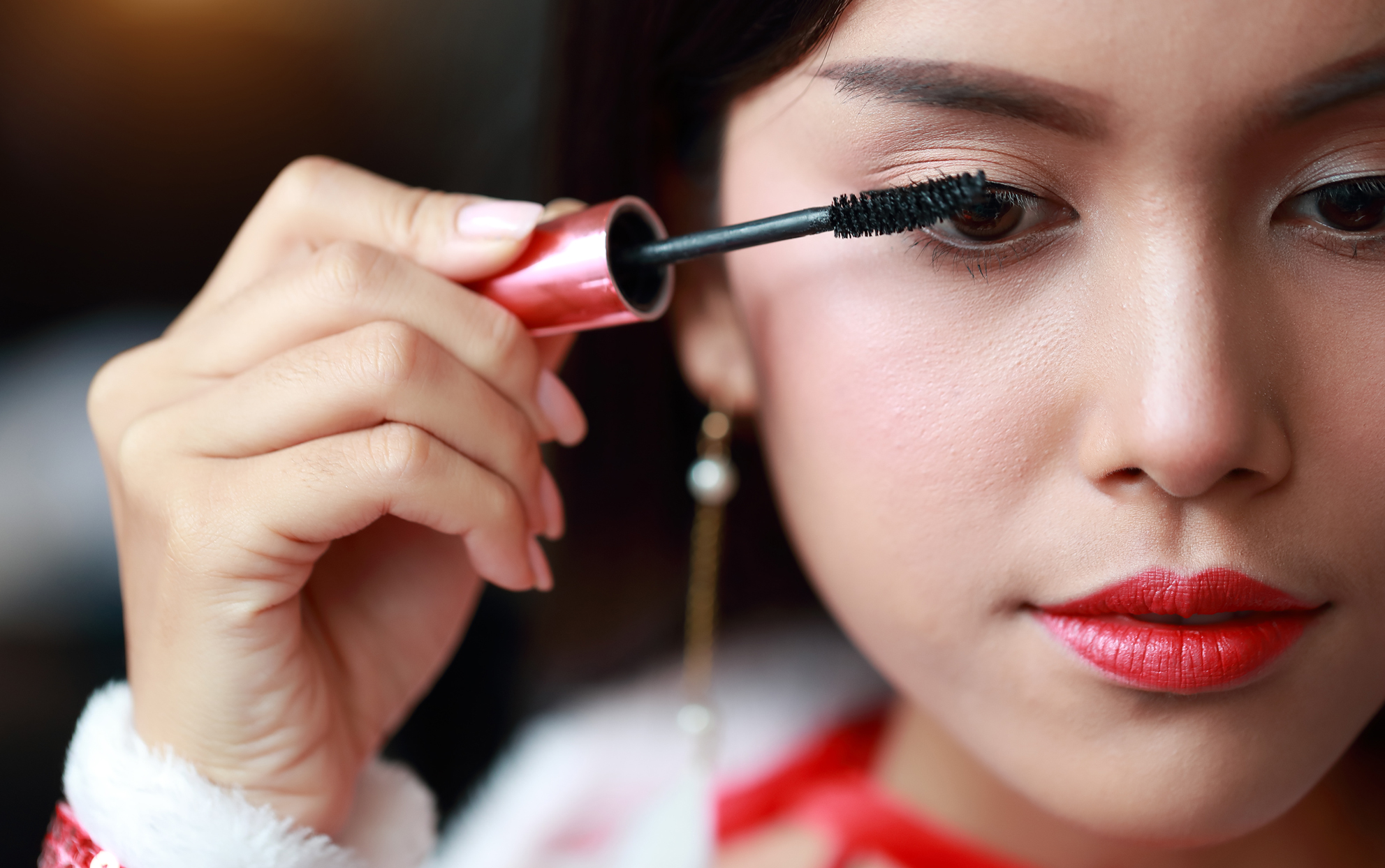 Close up of an Asian woman applying mascara