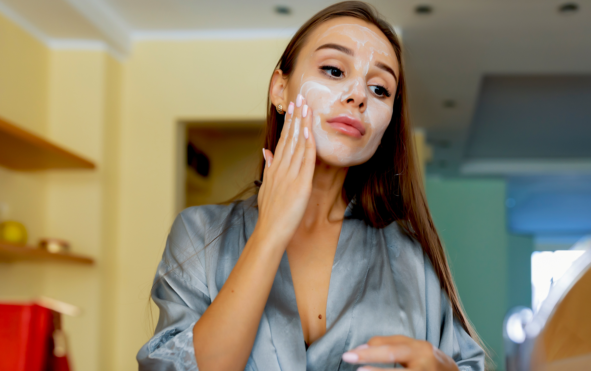 Woman applying a creamy face mask to her skin