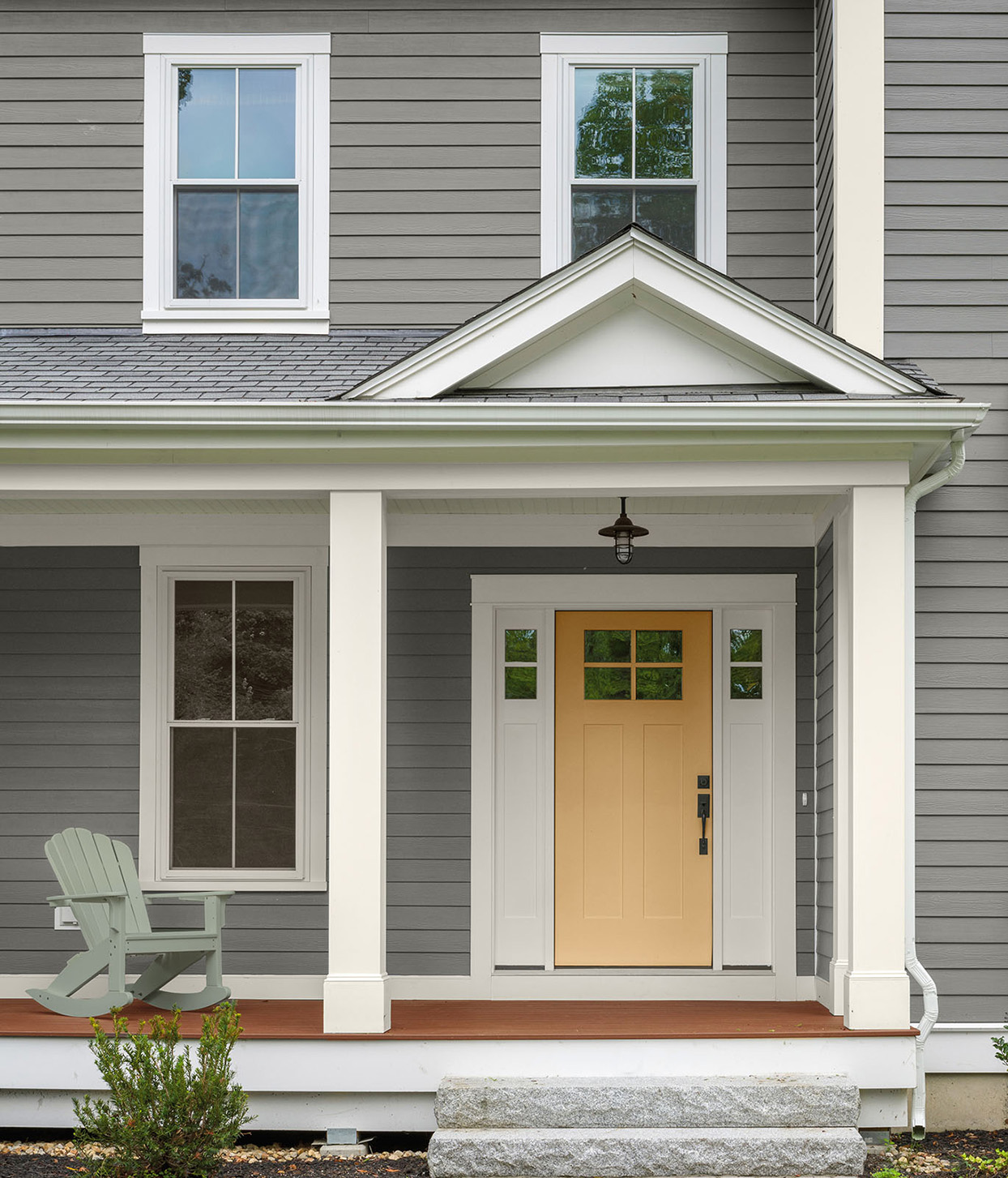 gray home exterior with yellow front door