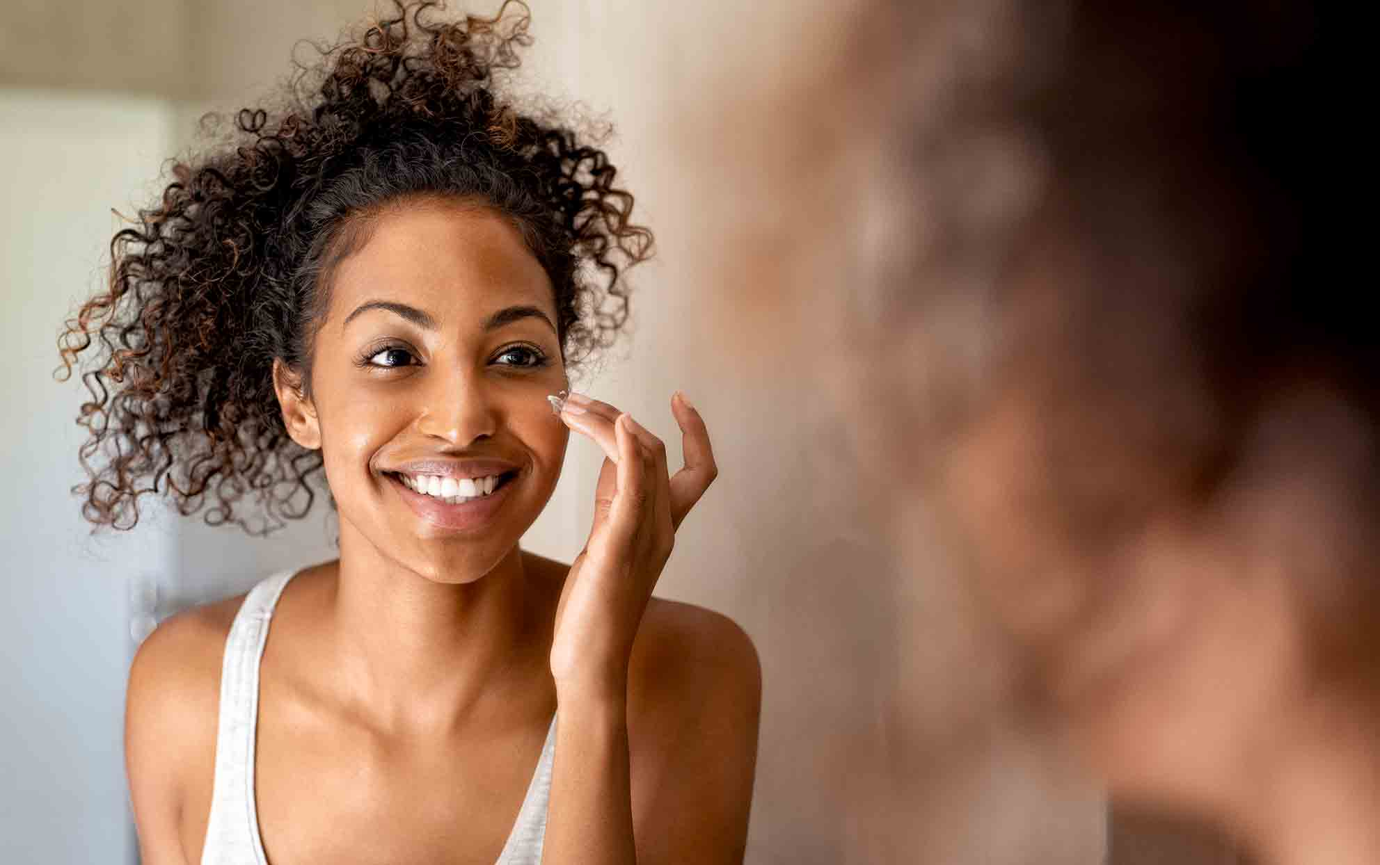 African American woman applying face moisturizer in the mirror