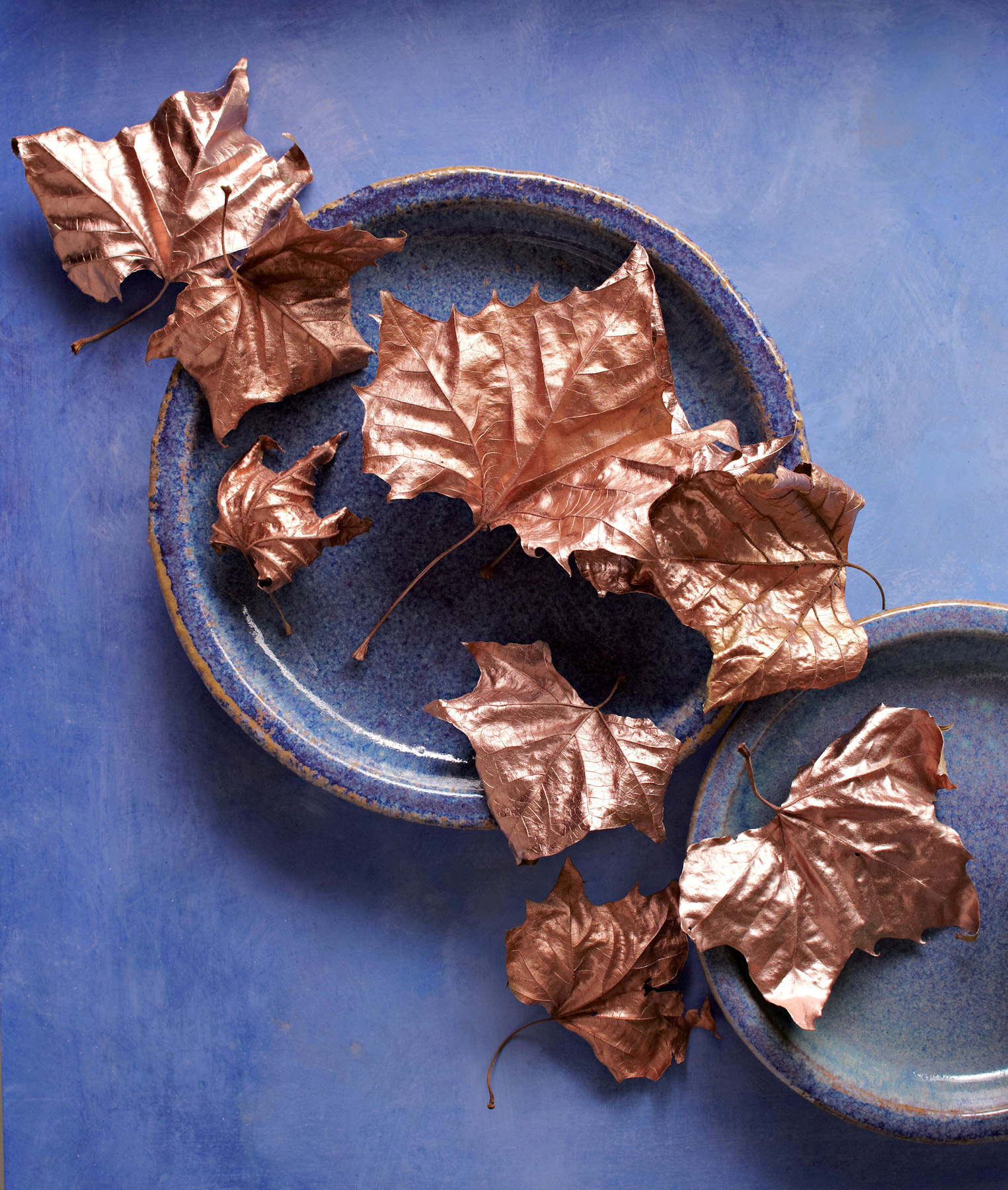 gold metallic painted leaves on blue plates