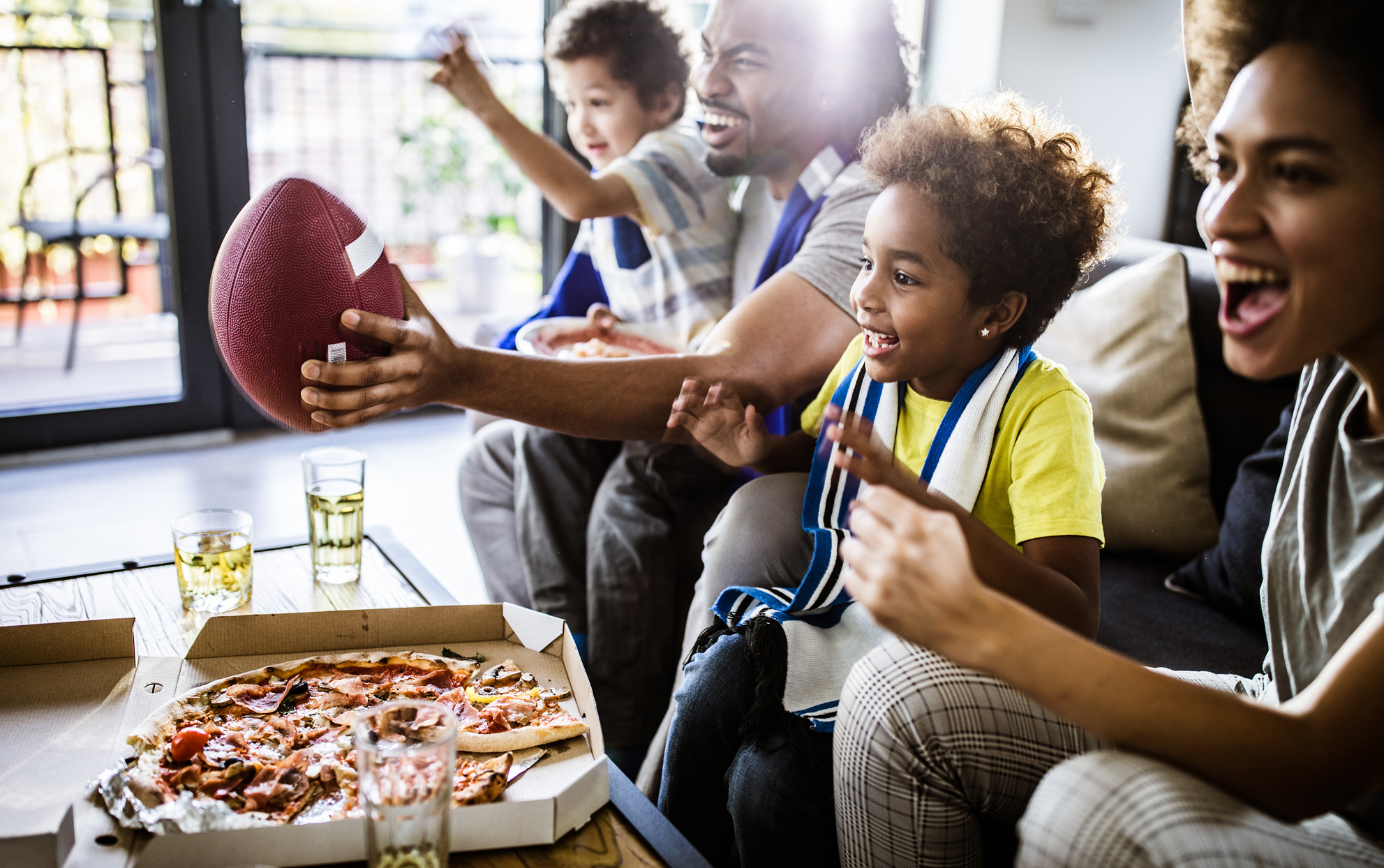 Ethnic family watching football on tv and eating pizza at home