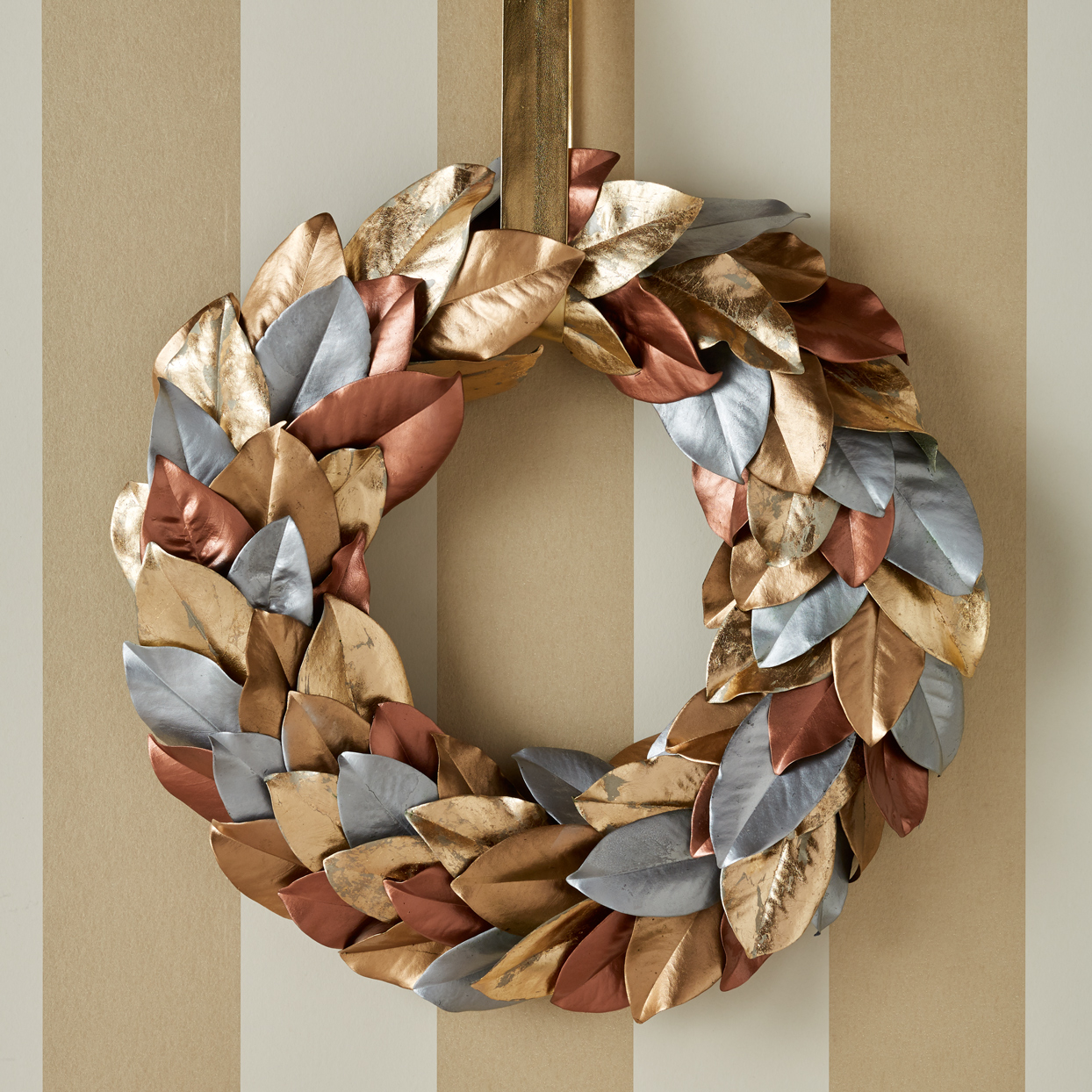 metallic-painted magnolia leaves wreath hanging on striped wall
