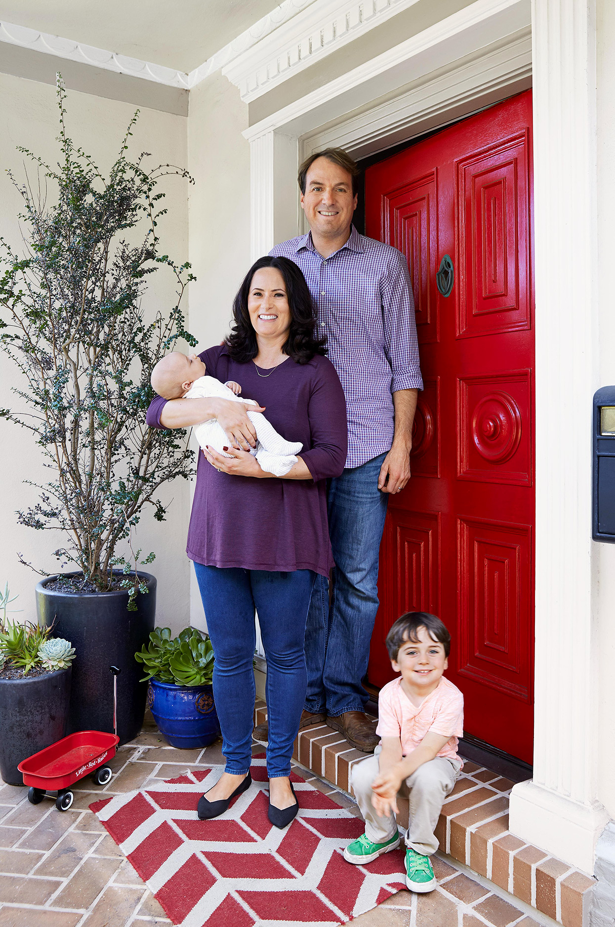 family of four portrait outside house in front of red exterior door