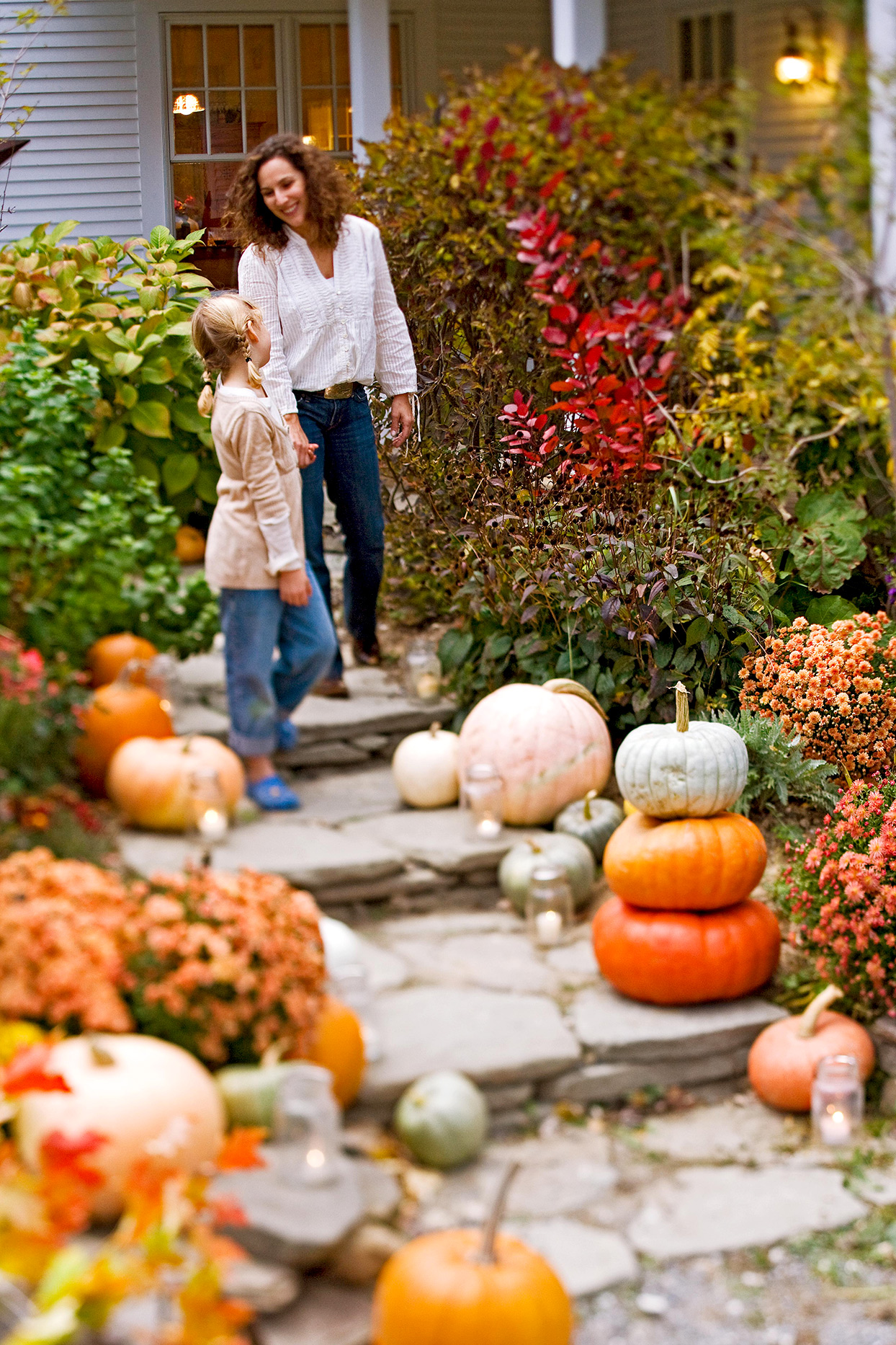 adult and child walking down path with pumpkins