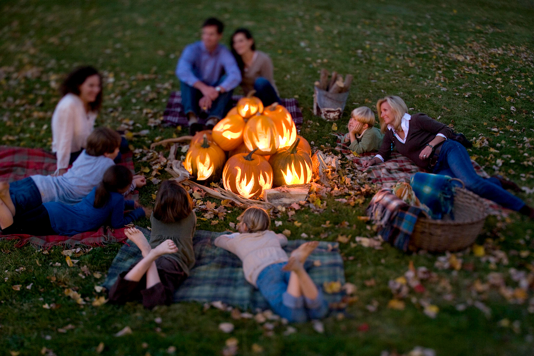 people lying around pile of lighted flame designed pumpkins