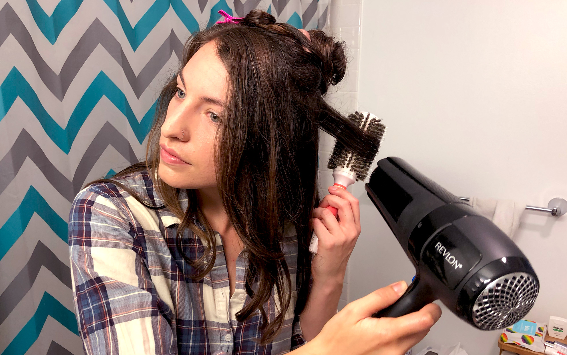 Young woman blow drying her hair in a bathroom
