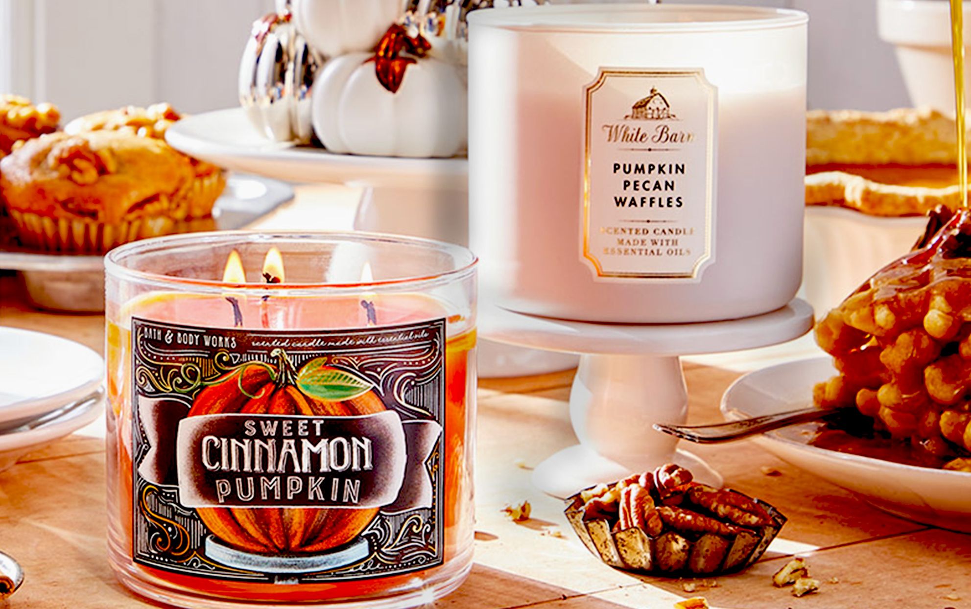 Two Bath & Bodyworks Fall candles on a wooden table with desserts