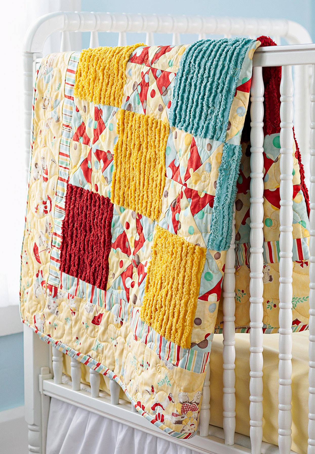 vintage-inspired pinwheel and chenille baby quilt on crib