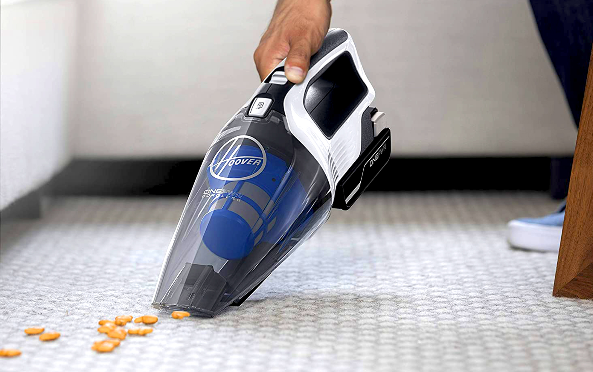 Hoover brand handheld vacuum being used on a carpeted floor