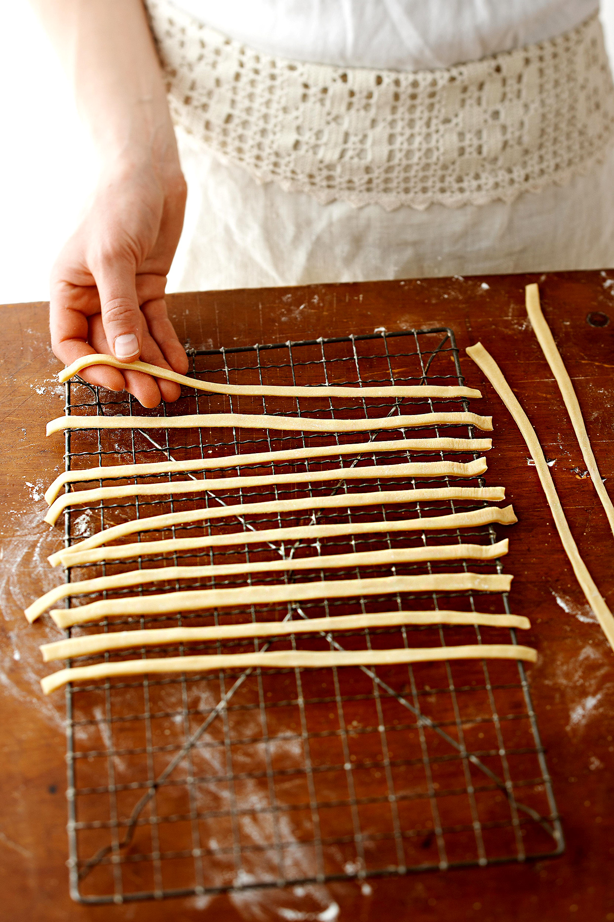 laying homemade noodle strips on wire rack