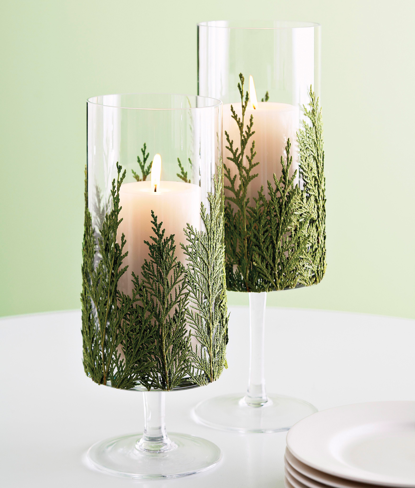 glass candleholders with greenery and white candles