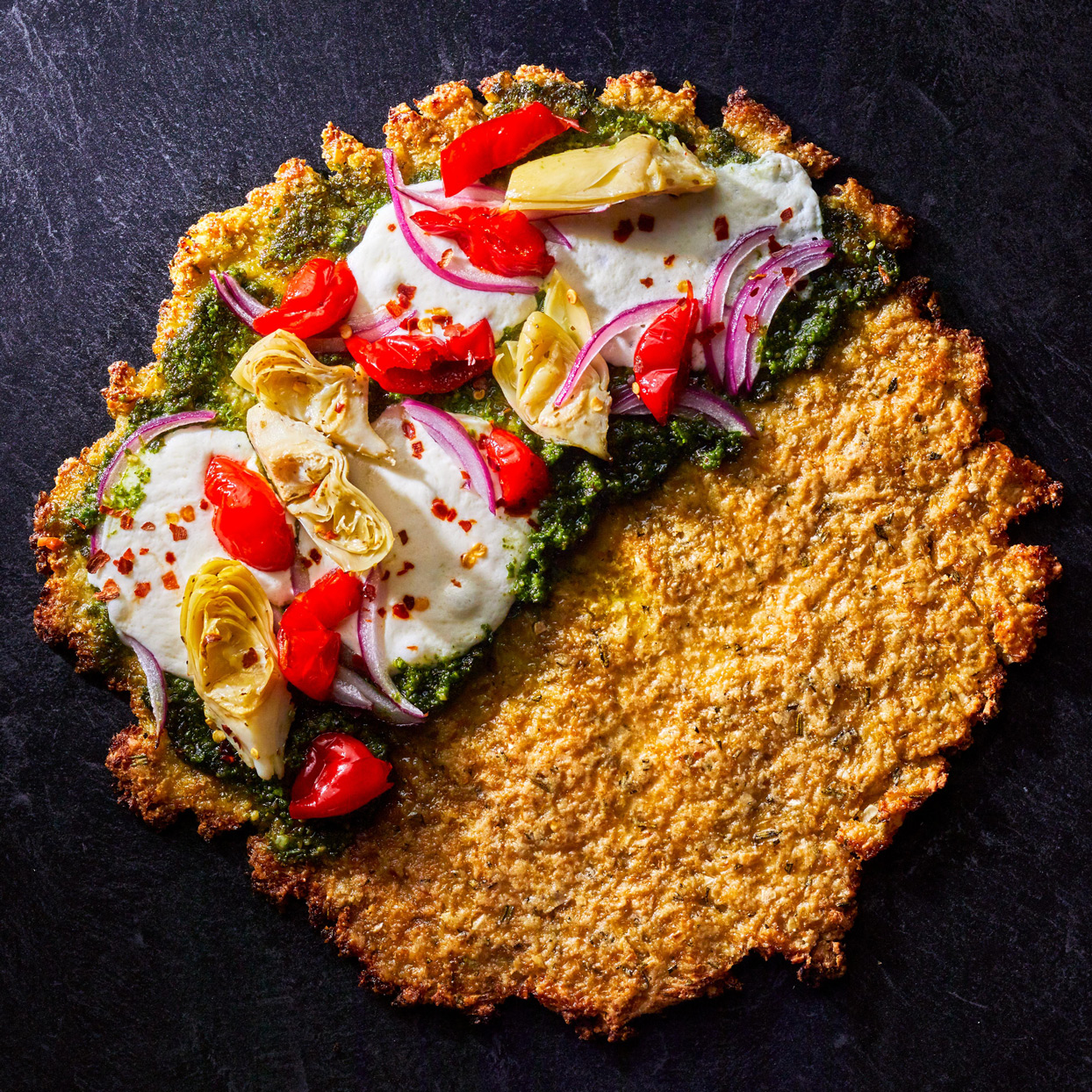 Cauliflower- and Rosemary-Crusted Pizza half covered with pesto, cheese, and vegetables