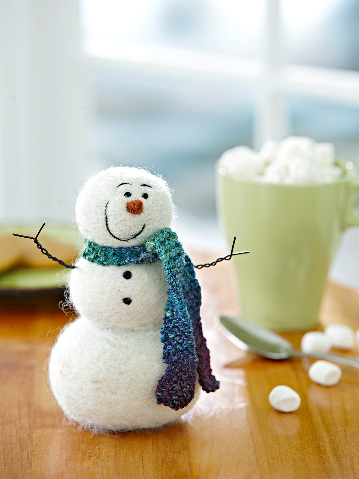 white smiling felted snowman with scarf on table