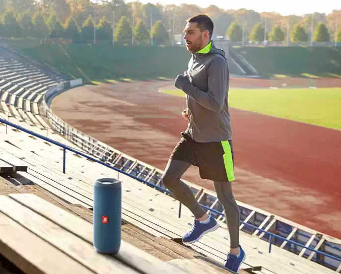 man running stairs at a football stadium next to a speaker