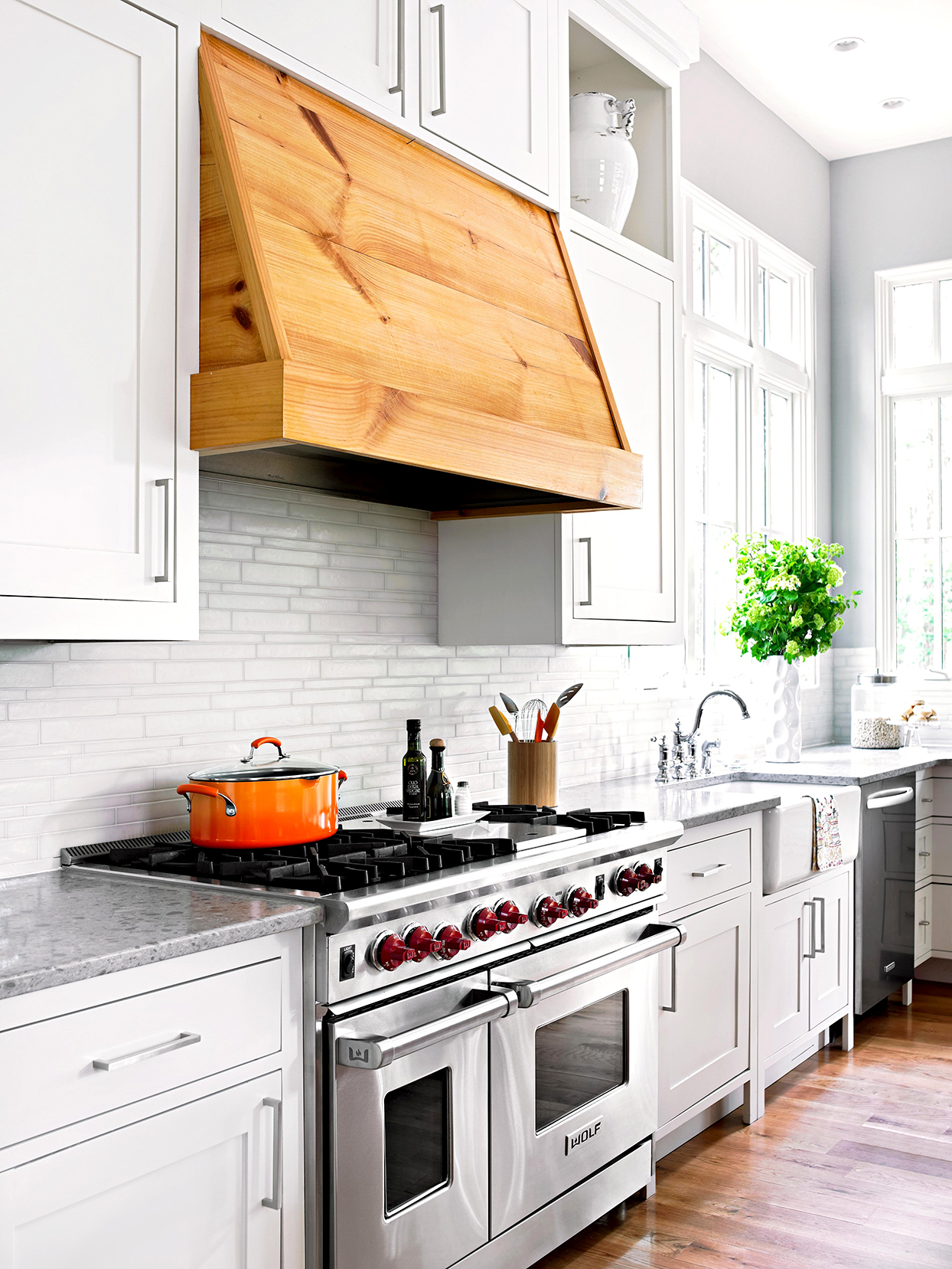 kitchen with white cabinets and wood hood