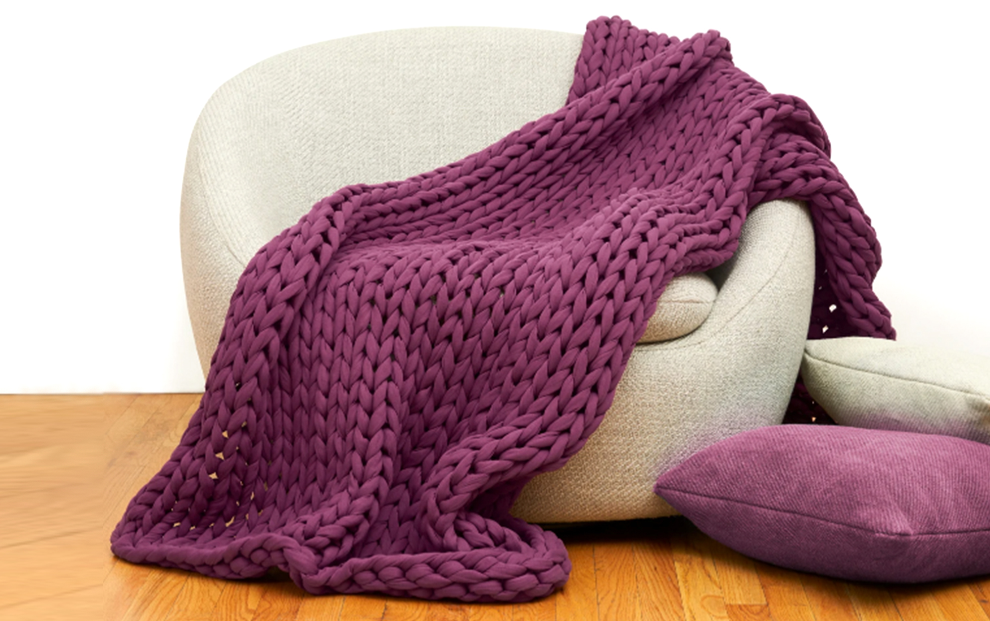Weighted knit eggplant colored blanket on a beige chair with pillows