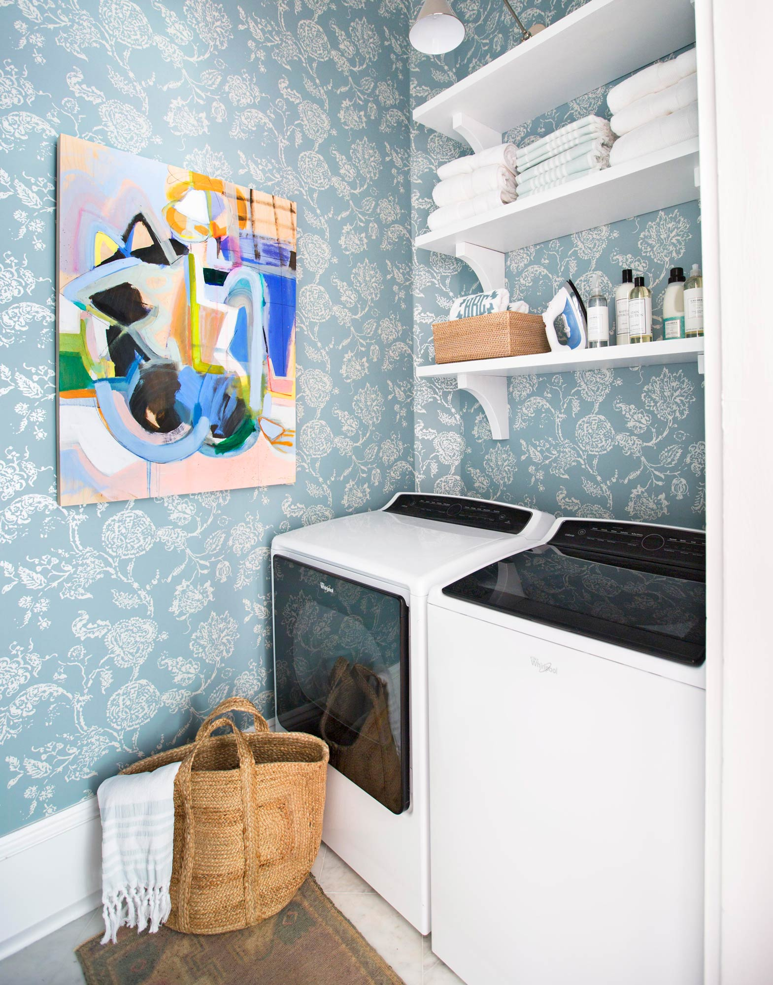 laundry room with shelves above washer and dryer