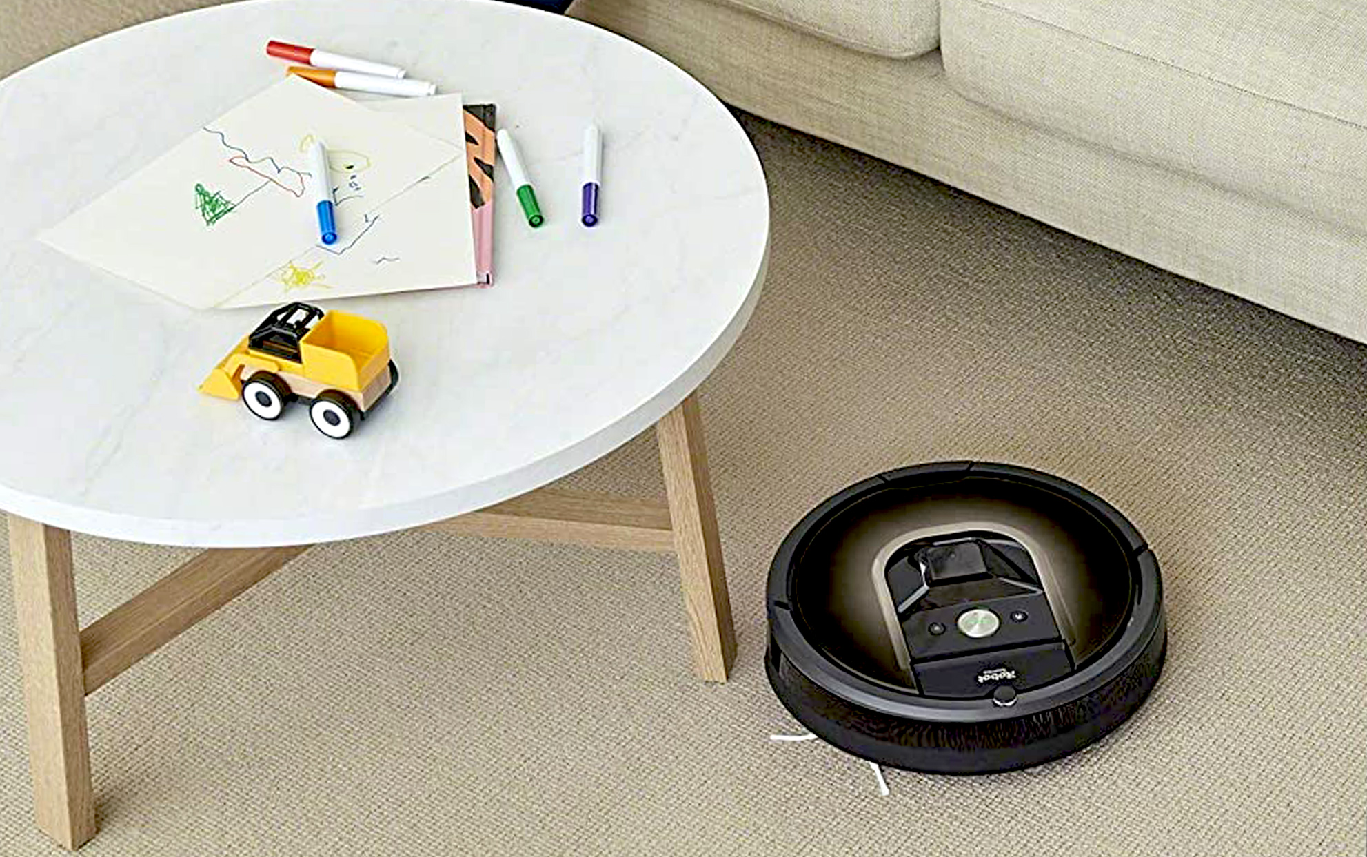 iRobot Roomba Vacuum on carpet near a sofa and table