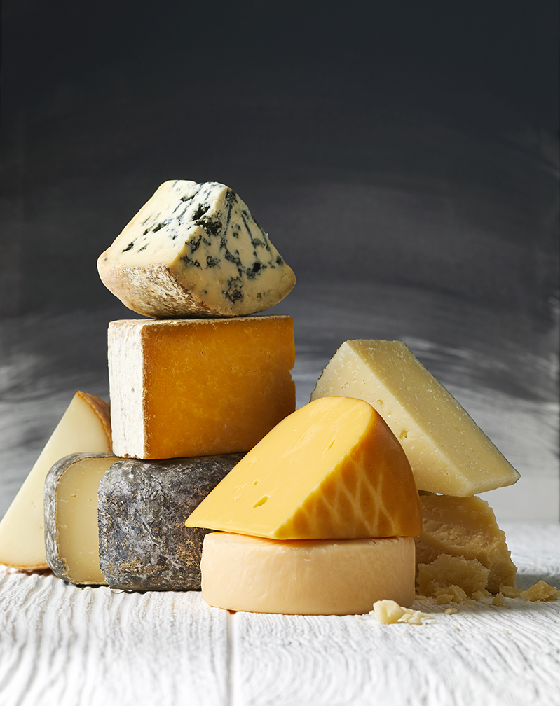 Variety of Cheeses Stacked on White Surface with Chalkboard Background