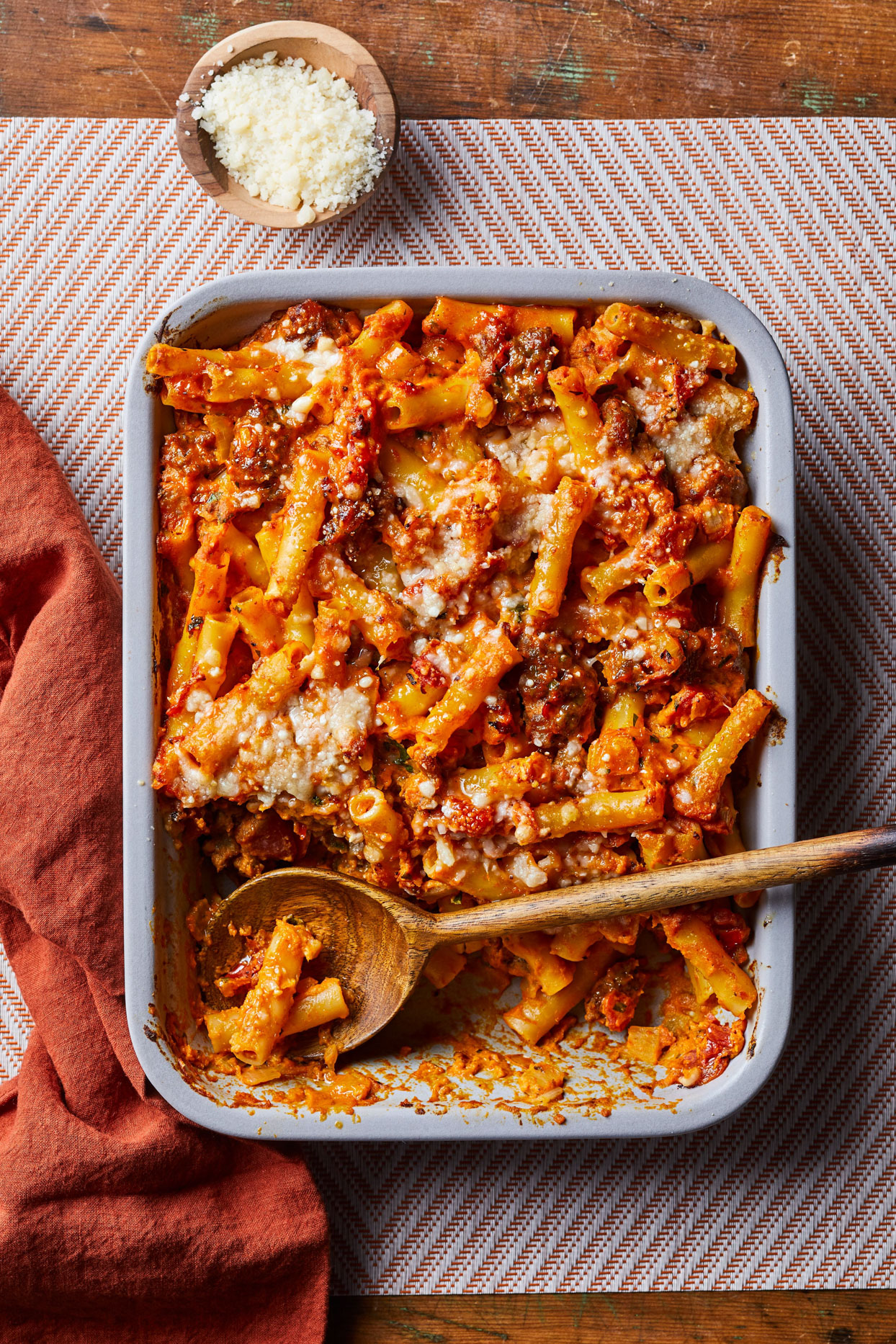 overhead view of Baked Ziti with Sausage and Pumpkin Tomato Sauce with wooden spoon