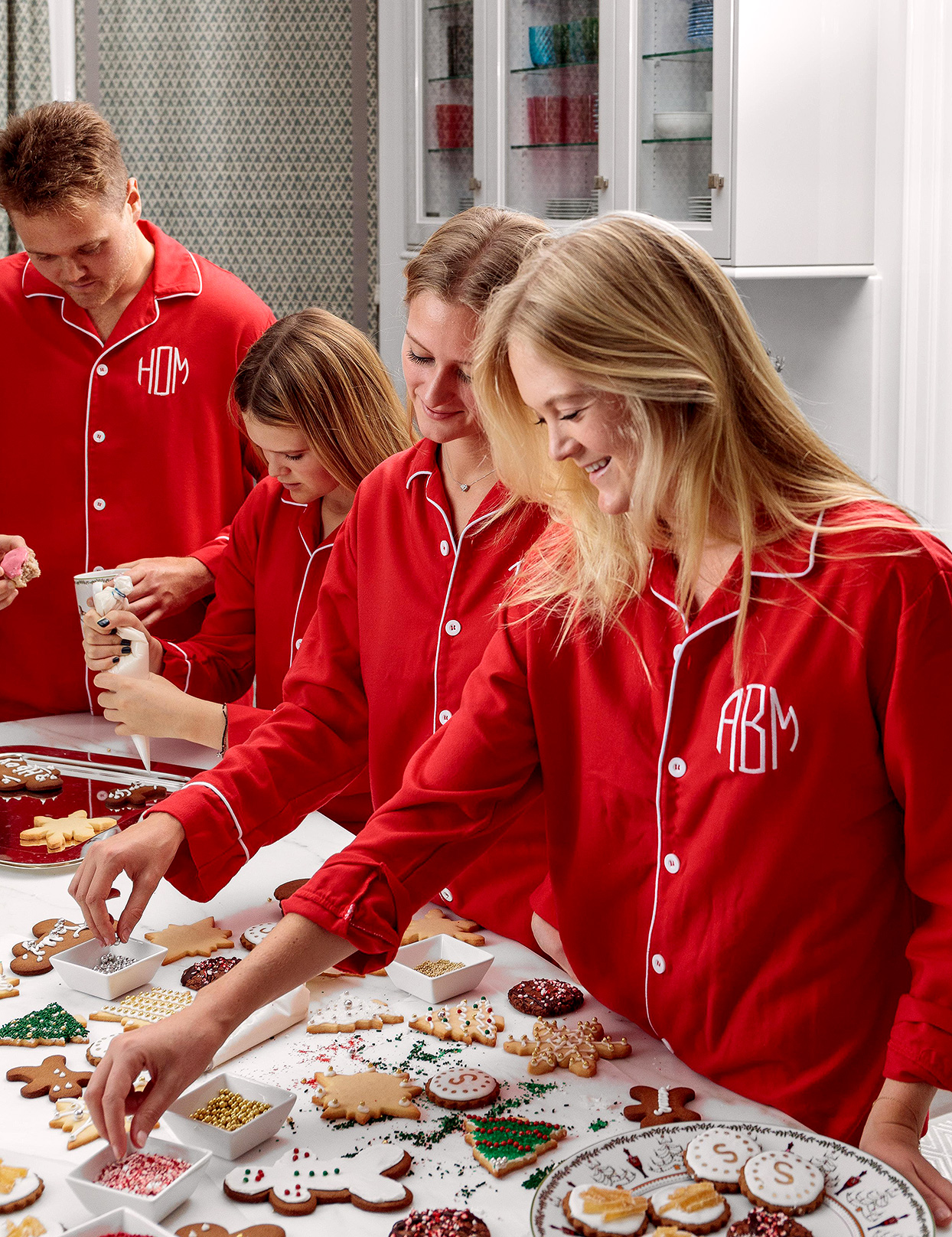 family in kitchen with red pajamas making holiday cookies