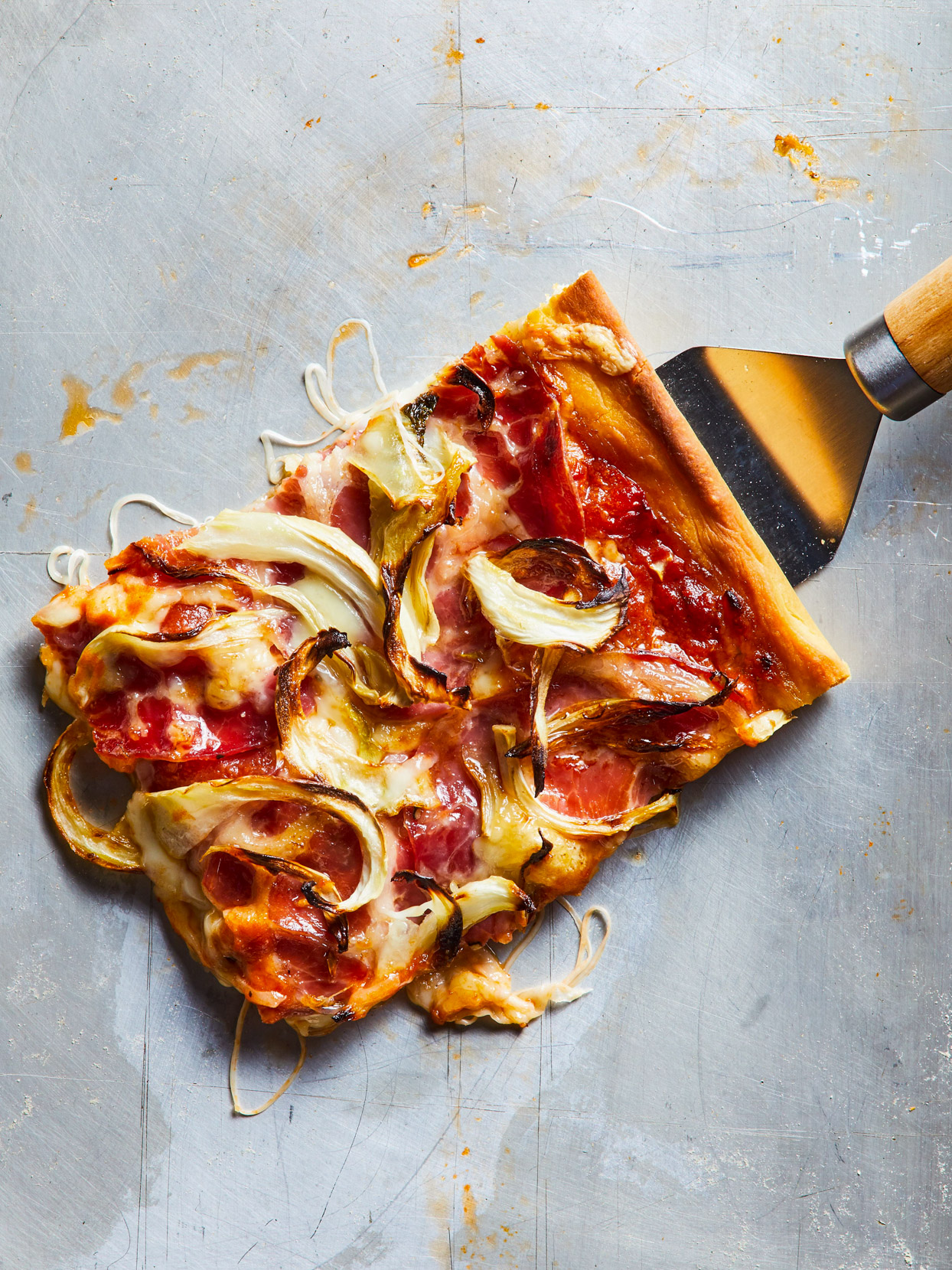 slice of Grandma-Style Pizza with Capicola and Fennel on spatula