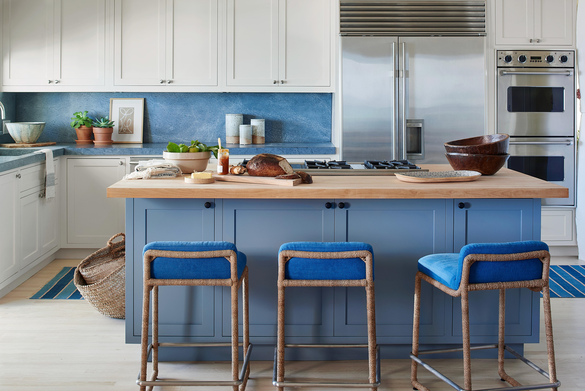 blue kitchen with wooden island and wicker chairs