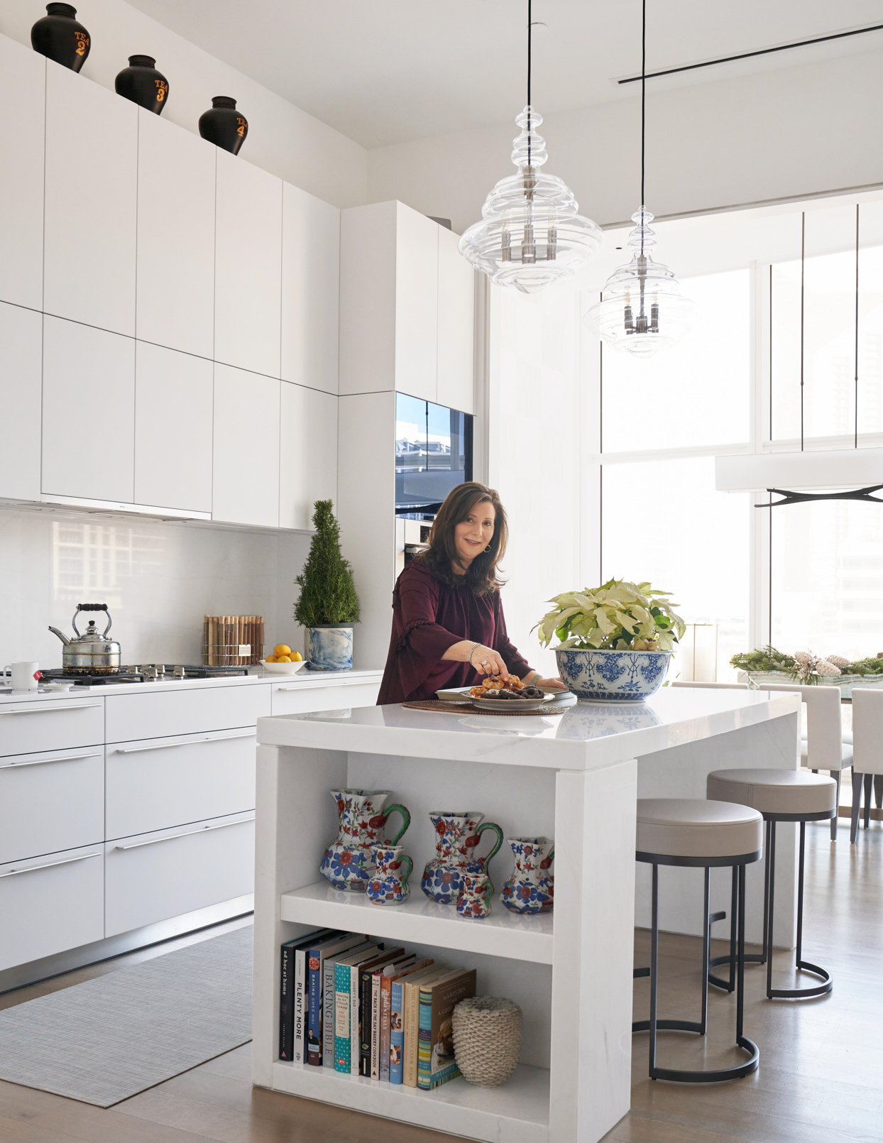 woman in modern white kitchen eating donuts